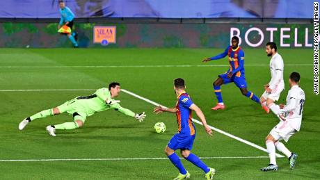Courtois dives for the ball during the El Clasico between Real Madrid and Barcelona.