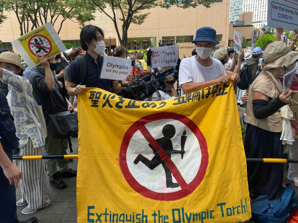 Protesters and followers collect in Tokyo because the Olympic torch relay reaches the ultimate